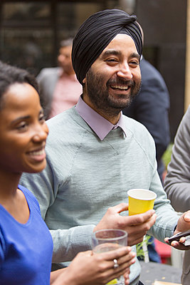 Smiling man in turban enjoying party - p1023m2009872 by Martin Barraud