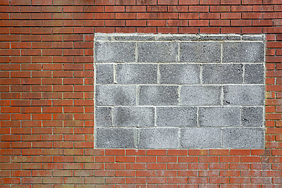 An old red brick wall with a section blocked in where there was a window with grey breeze blocks. - p1057m1332421 by Stephen Shepherd