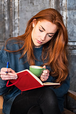 Young woman with long red hair sitting at table, holding notebook and cup of coffee. - p1100m2010837 by Mint Images