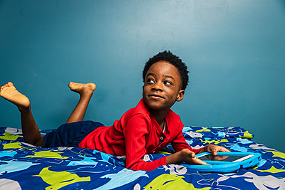 Boy looking away while using digital tablet on bed at home - p1166m2279357 by Cavan Images