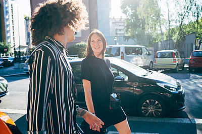 Couple talking while walking on city street during sunny day - p300m2206874 by Eugenio Marongiu
