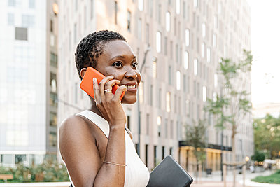 Smiling businesswoman with digital tablet talking on smart phone in city - p300m2299200 by COROIMAGE
