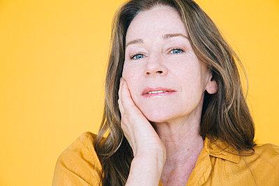 Portrait of senior woman against yellow background - p426m2205119 by Maskot
