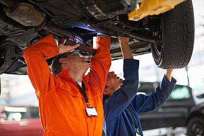 College mechanic students inspecting underneath car in repair garage - p429m1227075 by Peter Muller