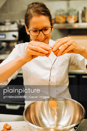 Female chef cracking eggs in a restaurant kitchen, lifestyle clo - p1166m2208080 by Cavan Images