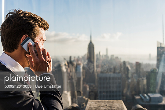 USA, New York City, man talking on cell phone on Rockefeller Center observation deck - p300m2013083 by Uwe Umstätter