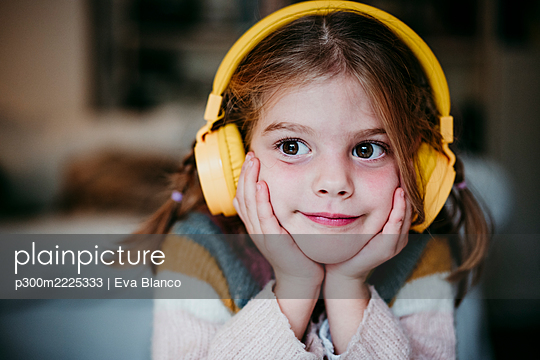 Cute girl with headphones and head in hands looking away while standing at home - p300m2225333 by Eva Blanco
