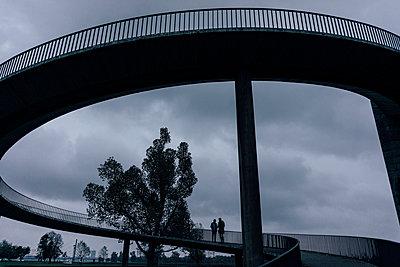 Two businessmen standing on dark bridge, having a meeting - p300m1537556 by Kniel Synnatzschke