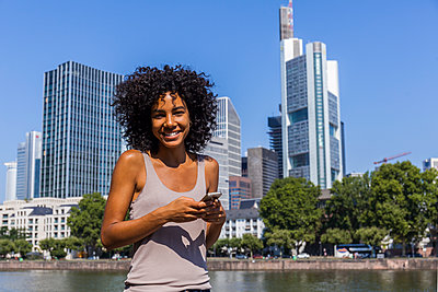 Germany, Frankfurt, portrait of smiling young woman with smartphone in the city - p300m2030285 by Tom Chance