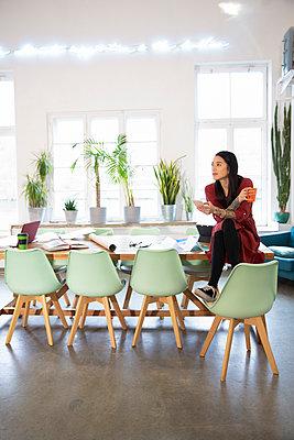 Woman sitting on table in modern office - p300m2114188 von Florian Küttler