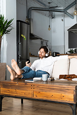 Relaxed man sitting on couch at home with cell phone and headphones - p300m2143977 by Giorgio Fochesato