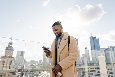 Stylish man using smartphone on observation terrace with skycraper view, Frankfurt, Germany - p300m2180004 by Hernandez and Sorokina