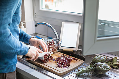 Crop view of man preparing salad in his kitchen - p300m2180445 by 27exp
