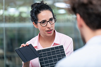 Businesswoman with eyeglasses showing solar panel model to male colleague in office - p300m2265184 by Florian Küttler