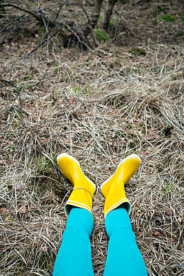 Woman in yellow rubber boots lies on forest soil - p427m1333075 by Ralf Mohr