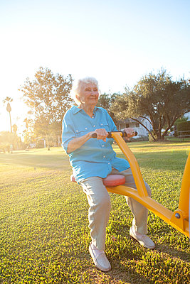Caucasian woman playing on seesaw in park - p555m1408859 by Shestock