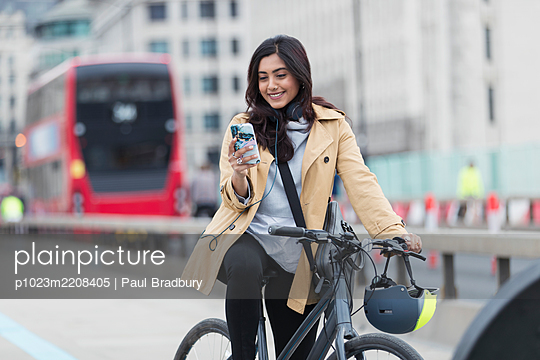 Smiling businesswoman using smart phone on bicycle in city, London, UK - p1023m2208405 by Paul Bradbury