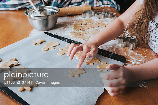 Young girl putting gingerbread man on baking tray - p1166m2137141 by Cavan Images