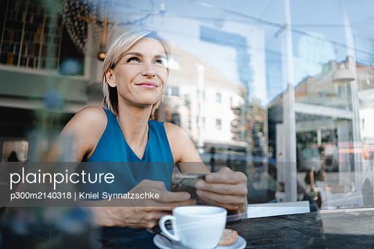 Businesswoman taking a break in coffee shop, holding smartphone - p300m2140318 by Kniel Synnatzschke