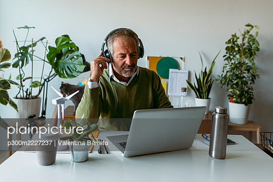 Man wearing headphones using laptop while sitting by table at home - p300m2227237 by Valentina Barreto