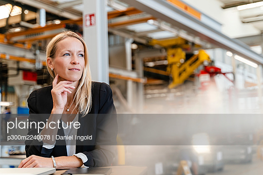 Smiling thoughtful businesswoman with hand on chin sitting in factory - p300m2240078 von Daniel Ingold