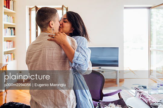 Young girlfriends kissing while embracing at home - p300m2294056 by Eugenio Marongiu