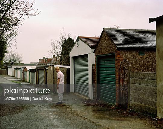 Woman sleepwalking by garages - p378m795568 by Daniel Keys