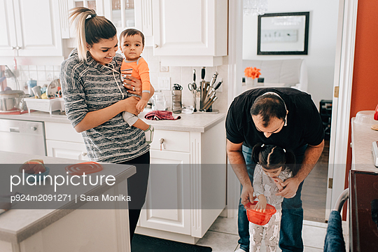 Mid adult couple in kitchen with daughter and baby son - p924m2091271 by Sara Monika