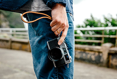 Midsection of young man holding camera while standing on street - p1166m1144650 by Cavan Images