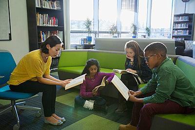 Teacher and elementary students reading in library - p1192m1016726f by Hero Images
