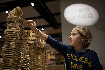 Girl stacking wood pieces in science center - p1192m1194233 by Hero Images