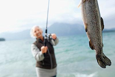 Germany, Bavaria, Walchsensee, Senior woman fishing in lake - p3007281f by Westend61