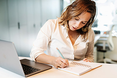 Businesswoman writing in notepad on desk at office - p300m2242904 by COROIMAGE