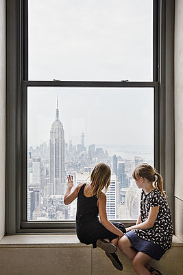 Girls looking through window at skyscrapers - p312m1228870 by Anna Kern