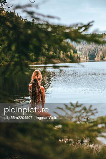Frau posiert vor ruhigem Bergsee - p1455m2204907 von Ingmar Wein