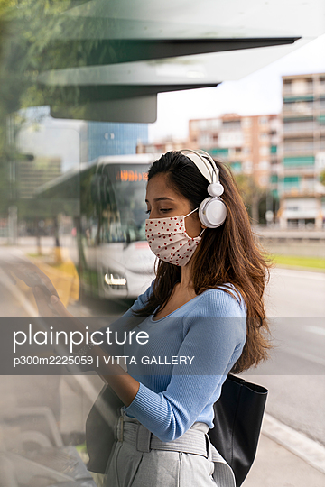 Woman in face mask wearing headphones while using smart phone at bus stand during COVID-19 - p300m2225059 by VITTA GALLERY