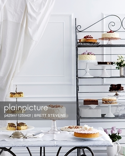 Selection of cakes on traditional tea table and stand - p429m1125940f by BRETT STEVENS