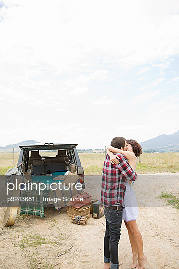 Couple kissing by suv