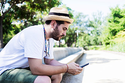 Smiling young bearded man sitting on bench using a smartphone - p1166m2137334 by Cavan Images