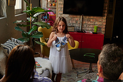 Girl in living room showing their parents her shoes - p1640m2242135 by Holly & John