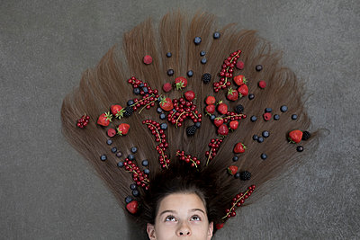 Portrait of girl lying on floor with fruits on hair looking up - p300m2062267 von Petra Stockhausen