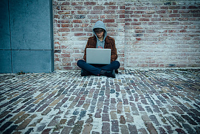 Teenager using laptop and sitting on a stone floor in the city - p300m2166247 by Annie Hall