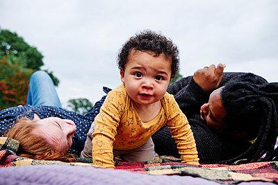 Carefree son crawling on picnic blanket at park - p300m2287366 by Angel Santana Garcia