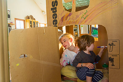 Caucasian boy and girl playing in cardboard house - p555m1491600 by Marc Romanelli