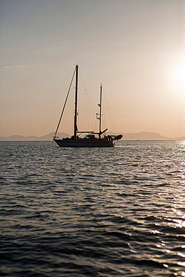 Silhouette of sailing boat at dusk - p575m805218f by Malcolm Hanes