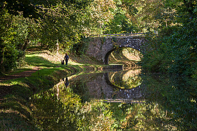 Young woman walking dog along a canal towpath in the Brecon Beacons National Park, Monmouthshire and Brecon Canal, Powys, Wales, United Kingdom, Europe - p871m1017465 by Adam Burton