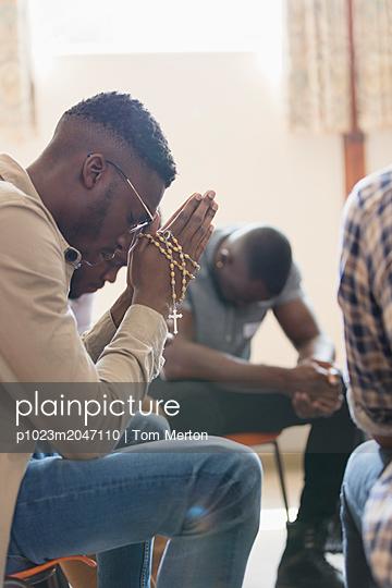 Serene man praying with rosary in prayer group - p1023m2047110 by Tom Merton