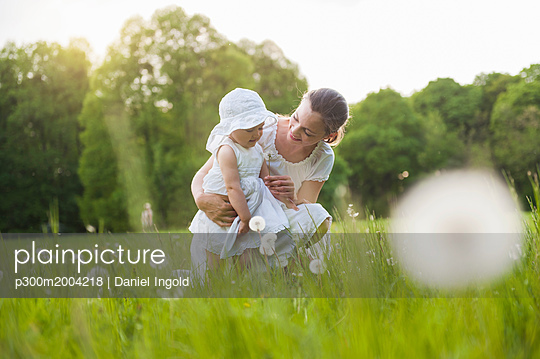 Mother and daughter with blowball on meadow in summer - p300m2004218 von Daniel Ingold
