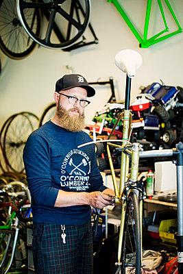 Hipster in Fahrradwerkstatt - p1195m1195467 von Kathrin Brunnhofer