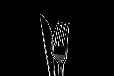 Clear plastic knife and fork against a black background. - p1302m1591692 by Richard Nixon